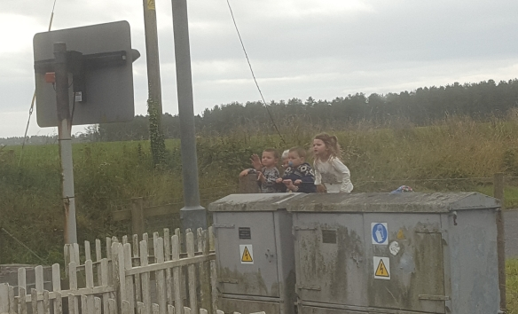 kids waving at the train